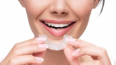 Woman putting in Invisalign | Dentist in Hampton VIC